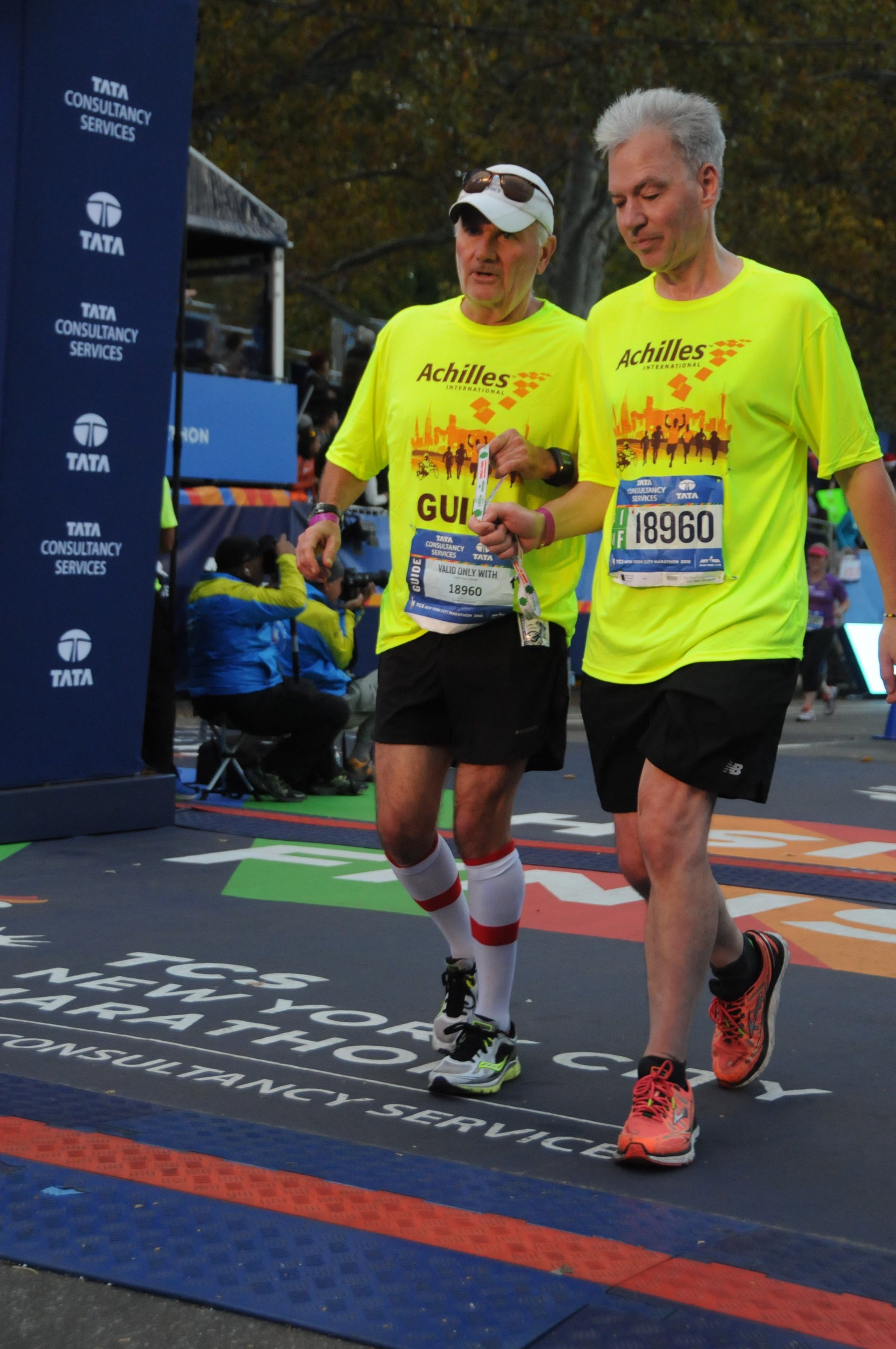 A male volunteer and a visually impaired athlete running together