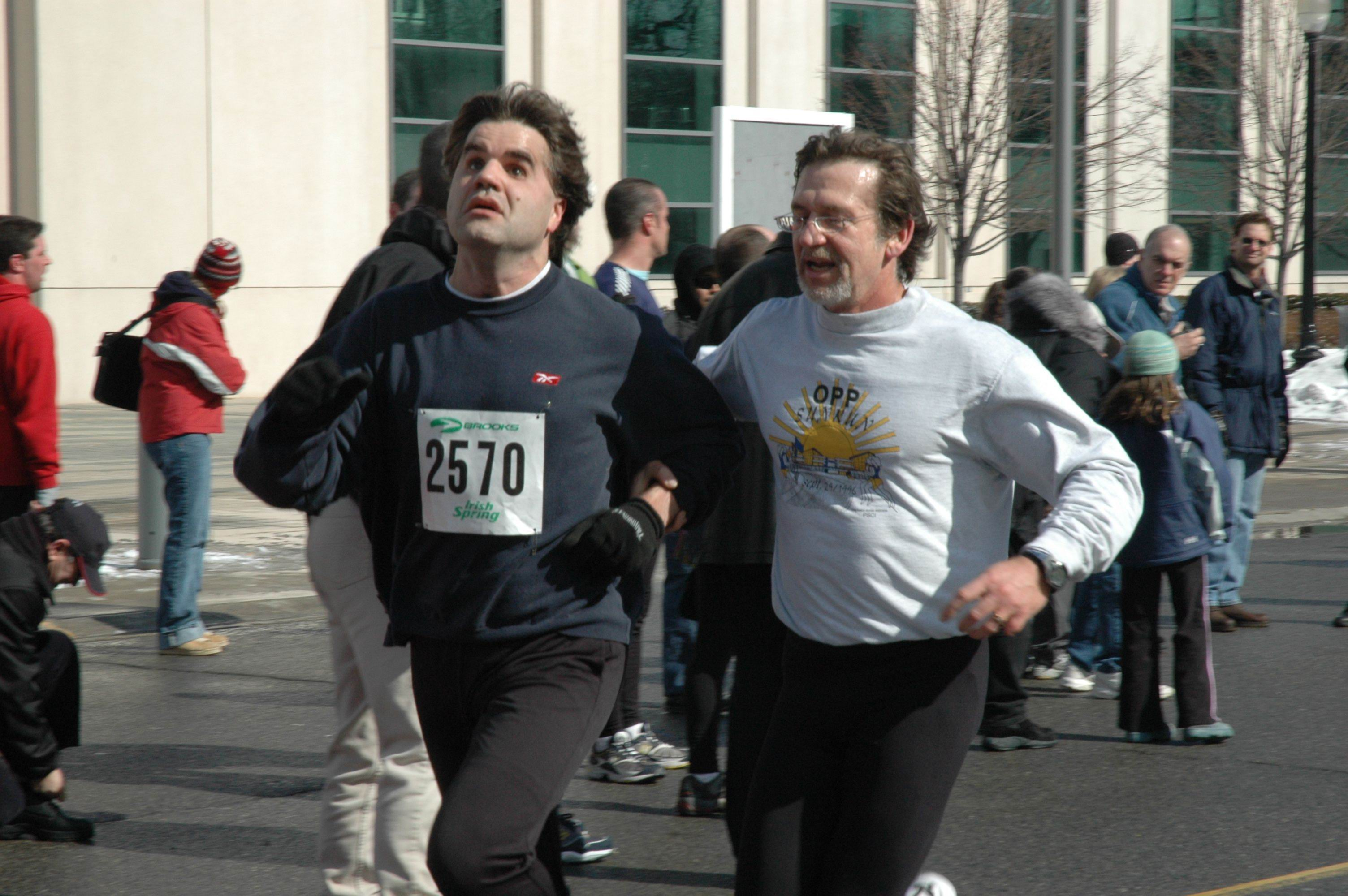 A male runner and a visually impaired runner participating in a marathon run