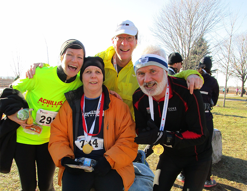 Four members of Achilles Canada have their picture taken after a run