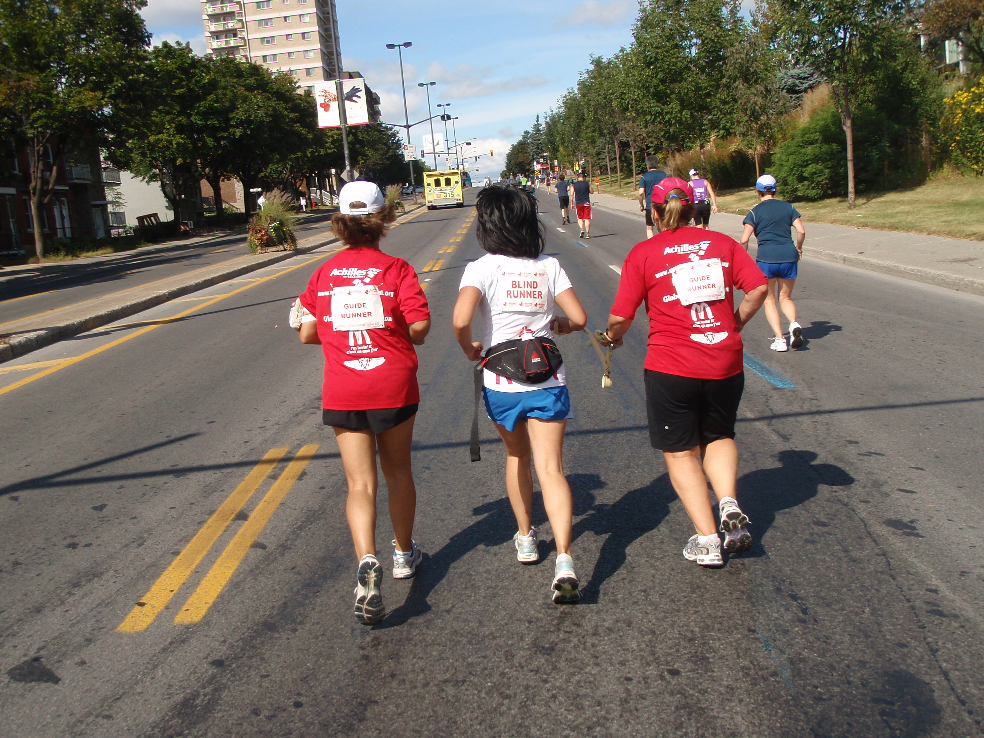 Two guide runners and visually impaired runner participating in a marathon
